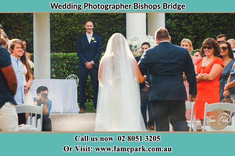 Photo of the Bride with her father walking towards to the waiting Groom Bishops Bridge