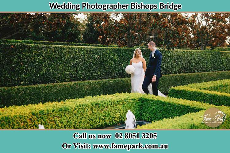 Photo of the Bride and Groom waiking at the garden Bishops Bridge