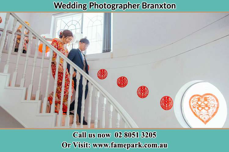 Photo of the Bride and the Groom walking down the stairs Branxton