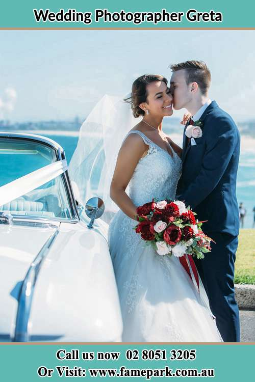 Photo of the Groom kissing his Bride beside the bridal car Greta NSW 2334