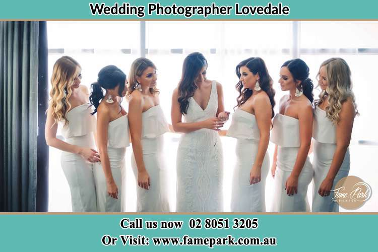Photo of the Bride with her bridesmaids looking at her Lovedale NSW 2325