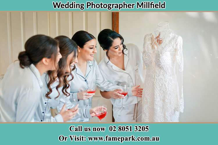 Photo of the Bride and her bridesmaids looking at her wedding gown Millfield NSW 2325