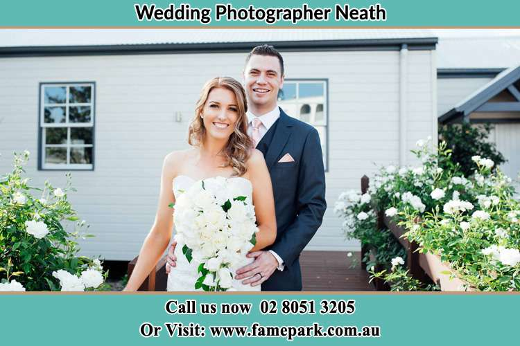 The Bride and the Groom smiling at the camera outside the house Neath NSW 2326