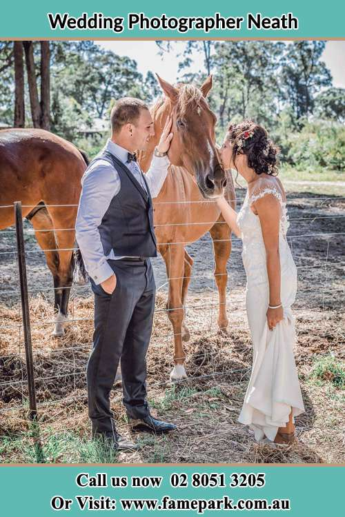 Photo of the Groom holding the horse while the Bride give a kiss Neath NSW 2326