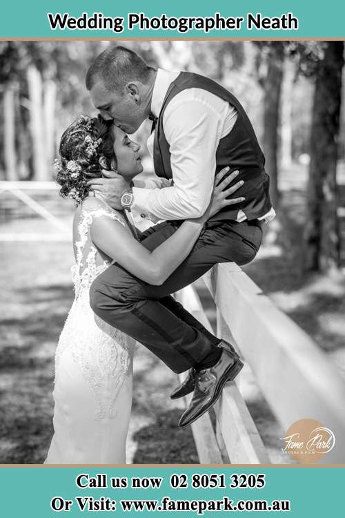Photo of the Groom sitting on the fence kissing his Bride at the forehead Neath NSW 2326