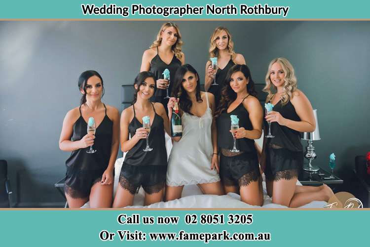 Photo of the Bride and her bridesmaids wearing lingerie holding wine on the bed North Rothbury NSW 2335