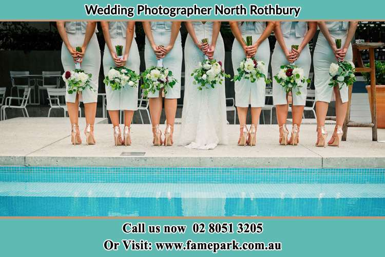 Photo of the Brides and her bridesmaids on their behind holding flowers near the pool North Rothbury NSW 2335