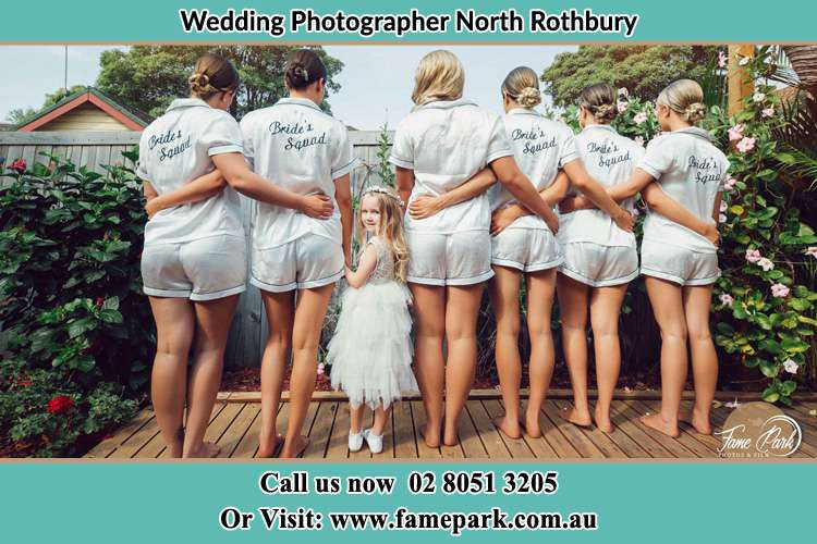 The Bride and the bridesmaids on their behind with the flower girl looking back the camera North Rothbury NSW 2335