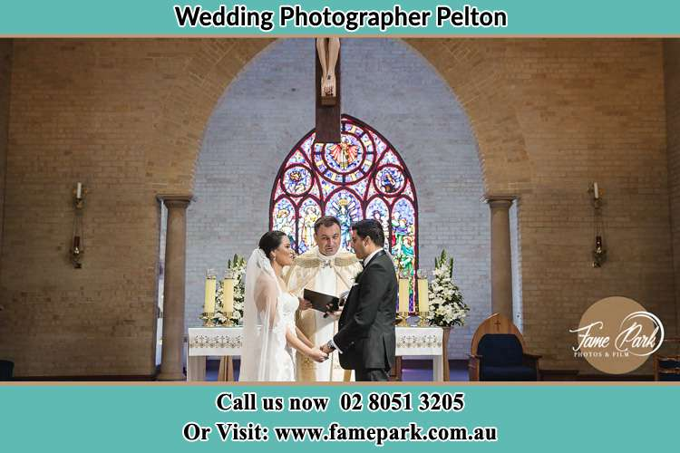 Photo of the Bride and the Groom with the priest during wedding ceremony Pelton NSW 2325